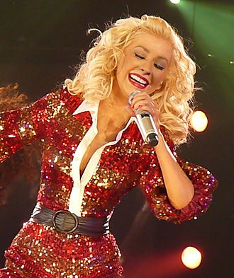 "Back to Basics Tour - Aguilera performed ""Makes Me Wanna Pray"" sitting atop a piano (left) and a reggae version of ""What a Girl Wants"" (right) in a red bodysuit"