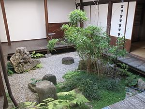 A garden courtyard with an en about 30 centimetres (12 in) above the pale gravel, feature stones, a rain chain, and a planting of bamboo, ferns, grasses, and a creeping plant with small round leaves.