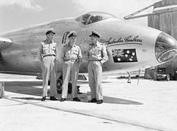 Black and white photograph of three men wearing military uniforms posing while standing in front of the nose of a military jet aircraft