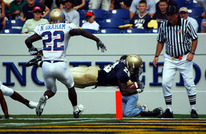 A player pursued by an opponent dives into the end zone in front of an official to score a touchdown.