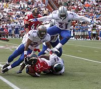 A running back being tackled when he tries to run with the ball.
