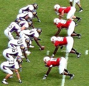 "American football positions - The four defensive linemen (in red) have their hands on the ground in a ""three point stance""."