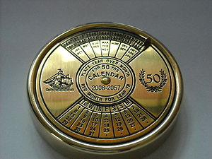 "Perpetual calendar - A 50-year ""pocket calendar"" that is adjusted by turning the dial to place the name of the month under the current year. One can then deduce the day of the week, or the date."