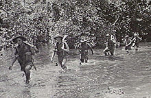 Soldiers wearing slouch hats and shorts wade along a watercourse