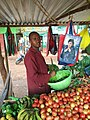 A young man chopping kales and other greens ready for sale.jpg