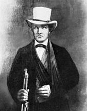 En mand i en mørk dragt med en hvid hat.  Hans venstre arm ser ud til at være i et slynge.  I sin højre hånd griber han fat i en rifle.