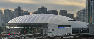 A distant shot shows a large domed arena set in front of a city skyline.