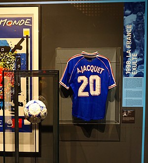 Aimé Jacquet - A France jersey emblazoned with Jacquet's name with the match ball used in the 1998 FIFA World Cup Final, on display at the Musée National du Sport.