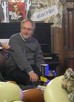 a bearded man with glasses, wearing a grey jumper, sitting on a sofa