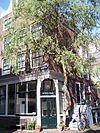 foto van Hoekhuis met halsgevel met geruite gedeelde vleugelstukken en een palmet in de afdekking