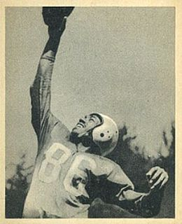 A black and white photo of Bob Mann reaching up with one hand to catch a football