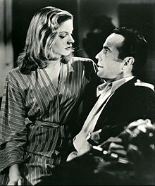 Lauren Bacall in black and white, sitting on Humphrey Bogart's lap facing right in the film To Have and Have Not in 1944