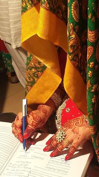Marriage in Islam - A Pakistani bride signing a marriage certificate
