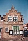 foto van Onder een nummer gecombineerd: geverfde lijstgevel 18e eeuw, met vernieuwingen en idem klokgevel 18e-19e eeuw. Rechts woonhuis, links winkelpui. Zijgevel aan Noorddijkstraat vernieuwd. Oude achterbouw