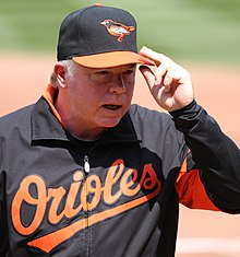 "A man in a black jacket with ""Orioles"" written across the chest in orange script letters and a black and orange cap with an oriole stitched on it touching the bill of this cap"