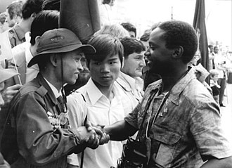 Provisional Revolutionary Government of the Republic of South Vietnam - A youth representative of the PRG greets a young man from a Soviet-aligned unidentified African nation. Both are attending a 1973 World Youth Conference held in East Germany and organised by the Free German Youth.