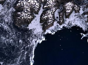 Cape Farewell, Greenland - Cape Farewell (in the centre of the image) and the rugged southern coast of Egger Island. The coast (dark) is generally surrounded by sea ice, making navigation treacherous.
