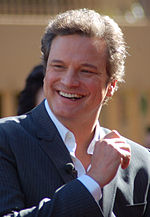 A brown-haired man is smiling. He wears a suit and a shirt, and he puts his right hand at chest height.