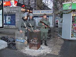 Stan wojenny, żołnierz i milicjanci przy koksowniku (współczesna inscenizacja)