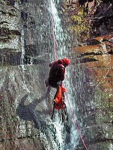 plan moyen d'un canyoniste avec son sac en dessous de lui