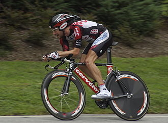 Time trial bicycle - A cyclist riding a time trial bicycle with aerodynamic wheels and aero bars.
