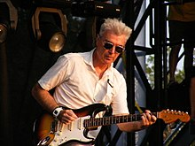 A closeup of Byrne playing guitar in a white suit and sunglasses