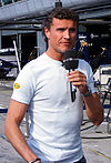 David Coulthard holding a microphone in his left hand speaking to the British media
