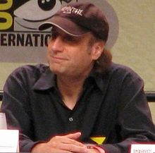 A seated David Mirkin wearing a cap smiles as he looks into the distance. His hands are crossed.