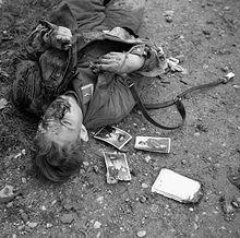 Photo noir et blanc prise le 23 décembre 1943 à Ortona, en Italie. Dans la partie gauche de la photo, le cadavre d'un soldat allemand gît (tête vers le bas de la photo) sur un sol de terre pierreuse. Trois photos de soldats sont visibles près de son épaule droite.