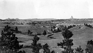Missouri Buttes - Devils Tower (right) and Missouri Buttes (left) on the horizon, viewed from the divide of Cabin Creek, 12 miles south. 1908 USGS photograph