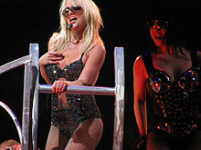 A female blond performer. She is wearing a sparkly black bodysuit and sunglasses. She also has a headset in her head. She is grabbing the bar of a jungle gym. In her right, a female is wearing sunglasses and a black corset with metal pieces.