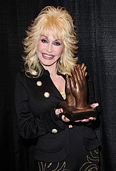 A blonde woman wearing dark clothing, holding a trophy in the shape of hands applauding
