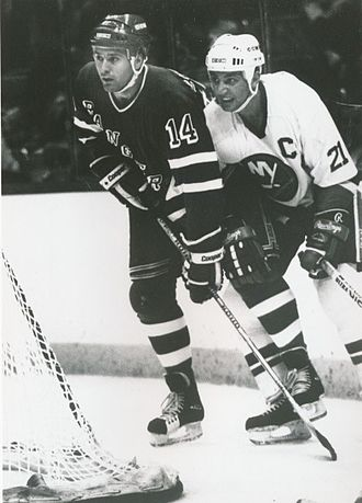 Brent Sutter - Sutter checking the Rangers' Doug Wickenheiser in 1988