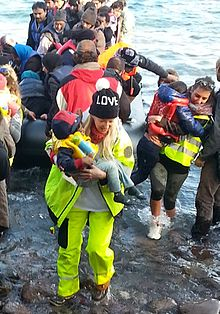 Alison Thompson is dressed in yellow emergency gear and a love cap. She is carrying a Syrian refugee baby to safety.