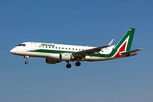 A white, green and red Embraer E175 aircraft in landing configuration.