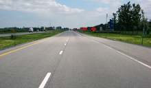 """A look down a rather level two-lane asphalt highway, with cars and trucks at some distance traveling in the same direction. Oncoming vehicles use the two-lane roadway some 3 or 4 metres to the left, separated by a grassy median. Orange signs and barrels to the right indicate construction work and farther to the right, a tall blue-and-white sign and flags welcome motorists to Quebec."""