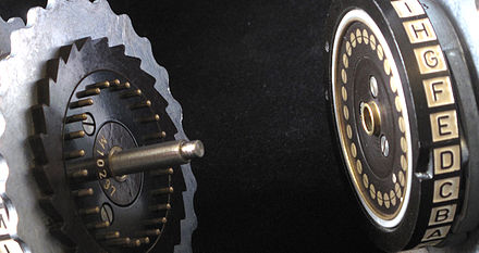 Two Enigma rotors showing electrical contacts, stepping ratchet (on the left) and notch (on the right-hand rotor opposite D). - Enigma machine