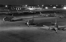 Jets lined up on a concrete ramp with buildings seen in the background