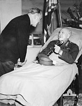 A man lies in a hospital bed, wearing an Army uniform instead of pyjamas. His peaked cap is on the blanket and he holds a baton in his hand. A man in a dark suit and pinstripe trousers bends over to talk to him. In the background are flowers, and a flag.