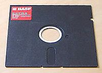"A 5¼-inch disk with a partly exposed magnetic medium spun about a central hub. The cover has a cloth liner to brush dust from the medium. Note the ""write-enable slot"" to the upper right and the strobe hole next to the hub that regulates drive speed."