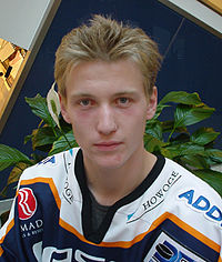 A frontal shot of an ice hockey player's head and shoulders. He has light brown hair and is wearing a blue and white uniform.