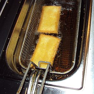 Deep frying - A close-up view of kaassoufflés cooking in a deep fryer