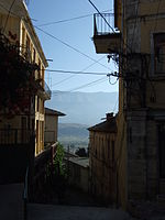 Gjirokastra - steep alley with power lines, behind Lunxhëria mountains
