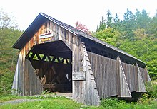 "A brown wooden covered bridge with pointed roof. Above its portal are signs saying ""Millbrook 1902"" and ""Pedestrians only"". To the right a faded sign says ""Safe load 6 tons"""