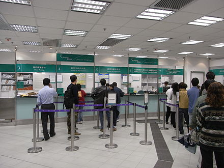 Post office queue. Operations management studies both manufacturing and services. HK Central Zhong Huan Zhong Xin The Center mall shop interior service counters queue line barrier visitors.jpg