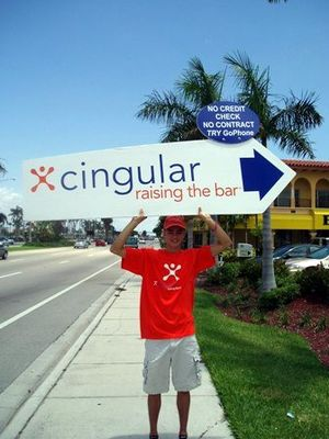 a human directional holding a sign for Cingular