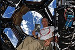 ISS-55 Drew Feustel holds Petr Ginz's 'Moon Landscape' inside the Cupola.jpg