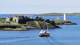 Inishbofin, County Galway - Inishbofin harbour, Port Island with Cromwell's Barracks and the light on Gun Rock, with Inis Goirt in the background.