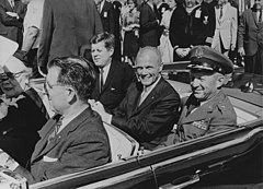A smiling Glenn in the back seat of a limo with John F. Kennedy and General Leighton I. Davis