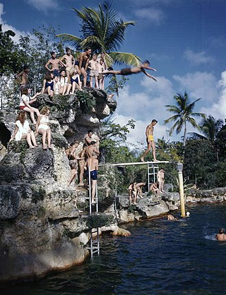 Venetian Pool - Kids diving off rock hill at the Venetian Pool tourist attraction in Coral Gables, Florida in the 1940s.